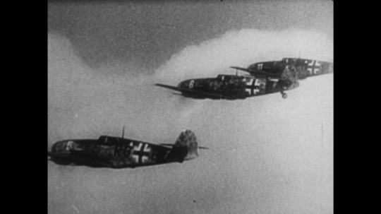 United States, 1940s: side profile of planes in flight during war. Planes fly in formation. Plane gets shot in sky. Bullets hit plane.