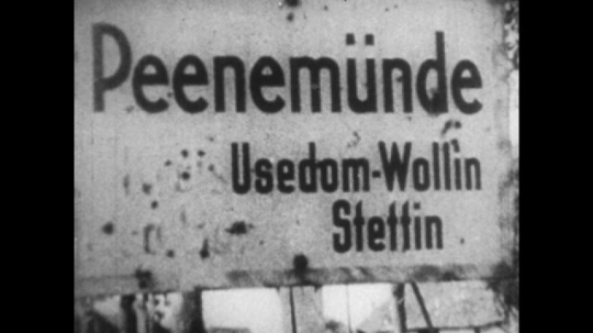 United States, 1940s: Sign for 'Peenemunde. Usedom-Wollin Stettin'. People walk from town. Rocket launched into sky. Rocket falls next to building. Explosion from rocket.