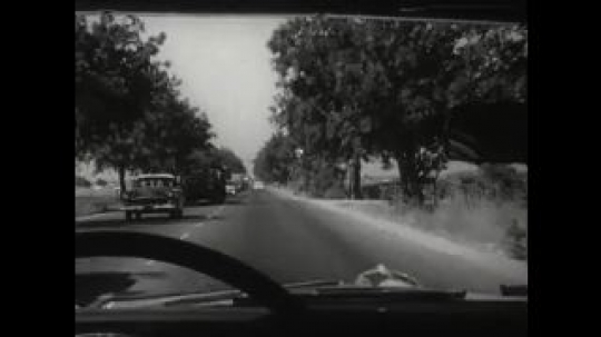 UNITED STATES 1950s: Inside of a car looking through the windshield as it travels down a busy road