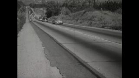 UNITED STATES 1950s: Busy road where a car approaching the camera safely pulls over into the hard shoulder and then stops