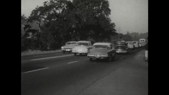 UNITED STATES 1950s: Cars travelling in both directions along a busy four lane road