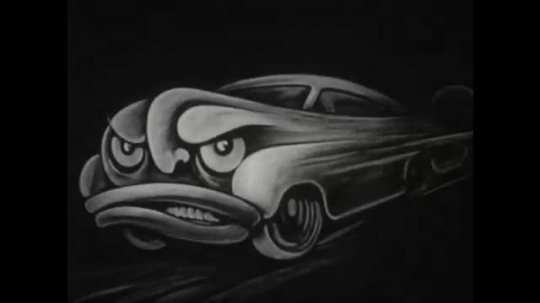 UNITED STATES 1950s: A caricature picture of a car where the front is an angry looking face. zoomed on a wheel of a car as it drives on a road