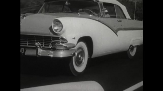 UNITED STATES 1950s: Car's front left side as it drives fast along the road. A close up of a car wheel as it drives on the road