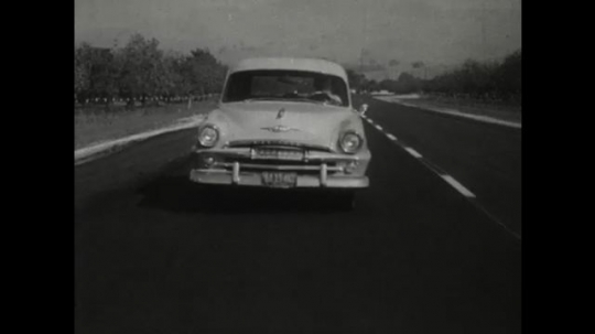 UNITED STATES 1950s: Front of a car as it travels down a two lane road. A close up of a steering wheel as a man struggles to safely control it