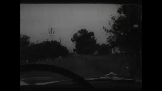 UNITED STATES 1950s: POV of a car as it drives fast along a country road. A slow moving tractor then pulls out in front of the car which causes the driver to suddenly brake