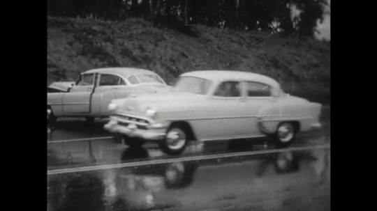 UNITED STATES 1950s: Cars in the rain slowly passing two wrecked cars on a four lane road. A scene looking from the side of the road as cars pass a