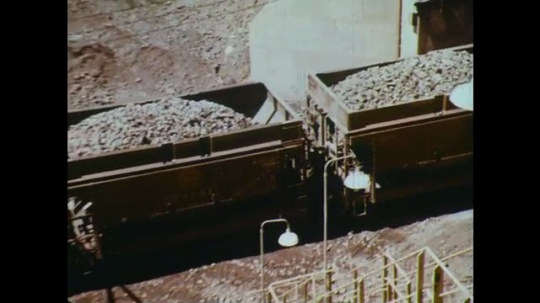 UNITED STATES: 1960s: train carries rocks on railway. Rocks in processing plant.