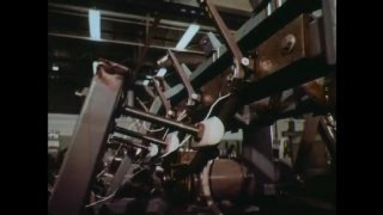 UNITED STATES: 1960s: machines in factory. Reflection of man in liquid. Lady looks down microscope