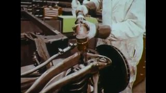 UNITED STATES: 1960s: man uses machine to screw bolts in car. Powder paint process. Man sprays paint.