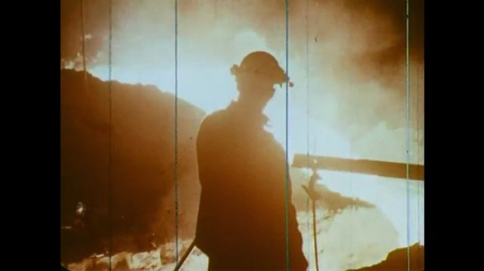 UNITED STATES: 1960s: man works in blast furnace. Sparks from molten metal. Flames in furnace. Silica sand fed into furnace.
