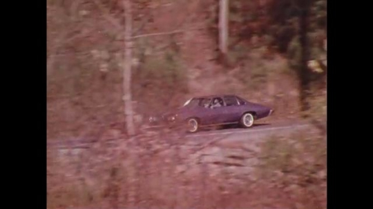 UNITED STATES 1970s: Car driving on road / Animation of engine / Car driving on bridge / Man talks to man in car, zoom out, car drives away / Zoom out on car lot.