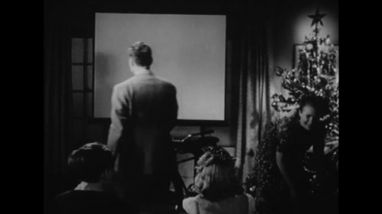 UNITED STATES: 1940s: lady talks to children by Christmas tree. Man clears away projector screen.