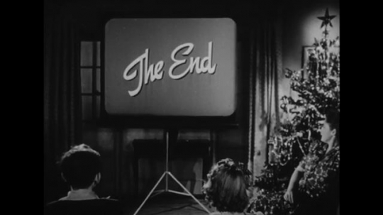 UNITED STATES: 1940s: Children watch movie on projector Screen. The End credits. Lady talks to children