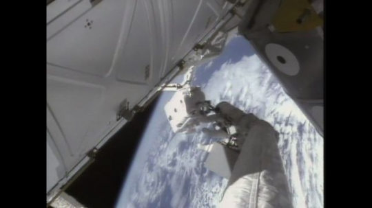 UNITED STATES: 1990s: astronaut works on outside of space station above Earth
