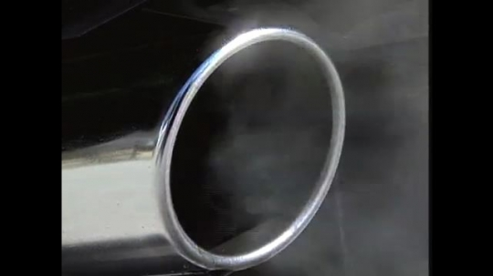 UNITED STATES: 1990s: close up of car exhaust and gas. Cars on road. Catalytic converter.