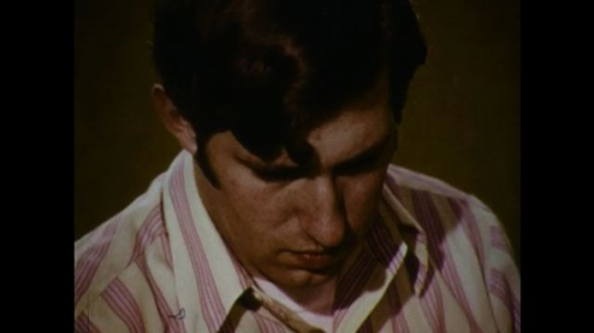 United States: 1970s: Close up of man blinking. Close up of wound on knee. Hand puts bandage over wound. Hands tie knot in bandage over wound. Cut and blood on injured arm.