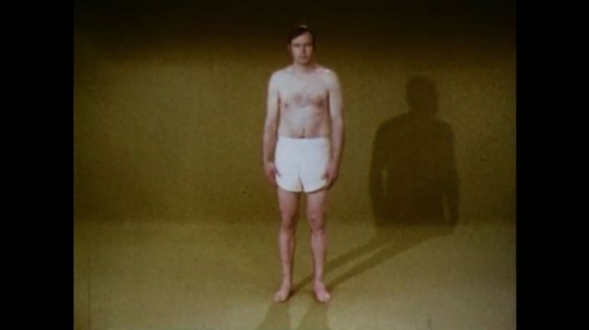 United States: 1970s: man in shorts stands in studio. Camera pans in to man