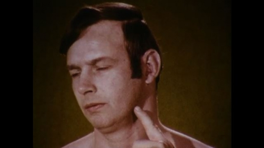 United States: 1970s: Fingers point to pulse point on neck of man. Close up of man