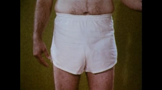 United States: 1970s: close up of man wearing shorts. Hand points for femoral area to find pulse. Man looks for pulse in thigh.