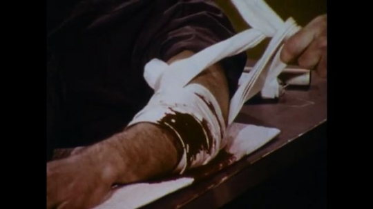 United States: 1970s: hands wrap bandage and pressure dressing around bleeding injury on arm. Hands tie knot in bandage. Man uses wood to twist bandage knot. Man checks pulse on arm.