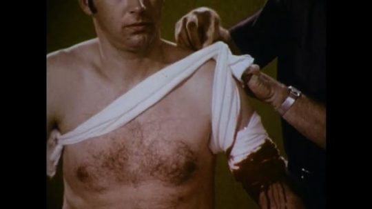 United States: 1970s: hands tie bandage over man
