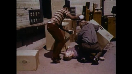 United States: 1970s: man collapsed underneath boxes. Men move boxes from casualty. First aider checks for response from injured man. Man undoes shirt of casualty. Man boxes boxes.