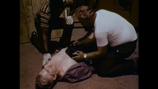United States: 1970s: man applies cold compress to chest of injured man. Man wraps shirt around casualty. Man covers injured casualty with blanket.