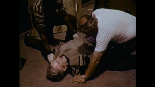United States: 1970s: men cover injured man with blanket and provide reassurance.