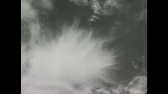 United States: 1940s: cirrus clouds in sky. Clouds above trees in sky. Cirrus stratum clouds in sky. Mackerel skies.