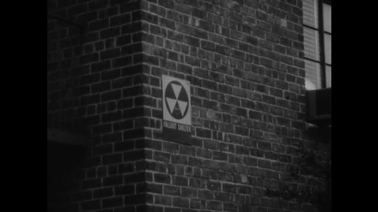 United States: 1950s: Radioactive symbol on brick building. View of street.