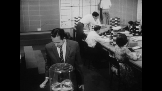 United States: 1950s: Man stands by water cooler. People work in office. Health and medical department. Lady talks on phone.
