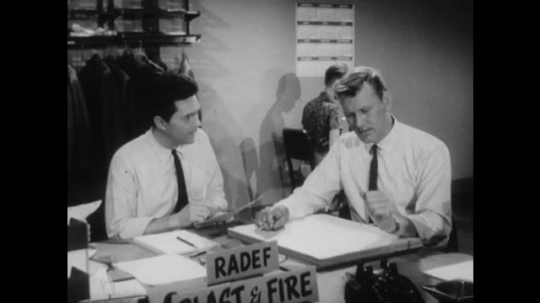 United States: 1950s: two men work at desk next to RADEF sign. Men discuss notes at desk.