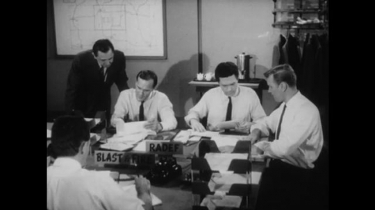 United States: 1950s: men discuss information at RADEF, Blast, and Fire desk. Close up of man