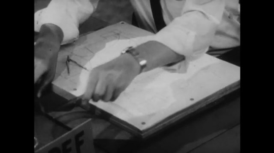 United States: 1950s: man picks up geometric stationary to draw on maps. Man lines up stationary on map. Men discuss paper notes. People work in RADEF office.