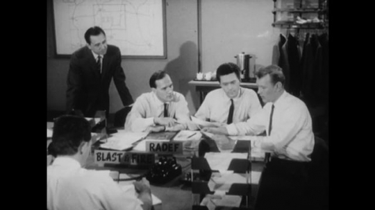 United States: 1950s: men work at RADEF desk. Man answers telephone at desk.