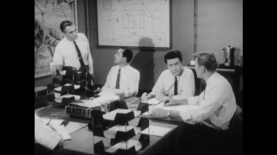 United States: 1950s: Men talk at office desk. Close up of man's face. Man makes telephone call.