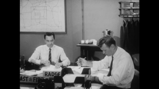United States: 1950s: Men work at communal desks in office. Man approaches colleague at desk. Man walks away from desk. Man at desk makes phone call.