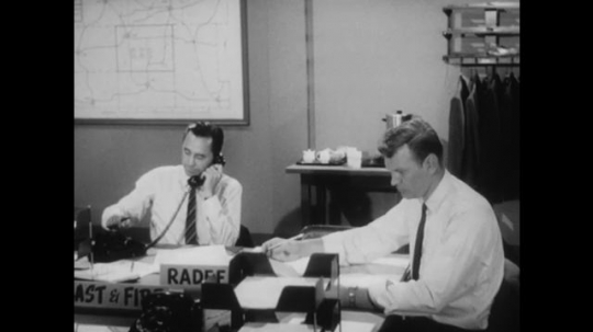 United States: 1950s: man at desk makes call. Man puts down phone receiver. Man reads paper at desk.