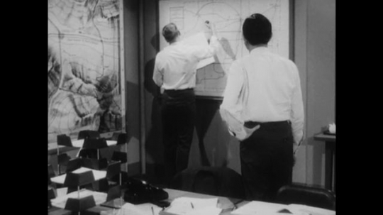 United States: 1950s: Man draws on whiteboard. Man gives paper update to colleague. Man tasks to colleague.