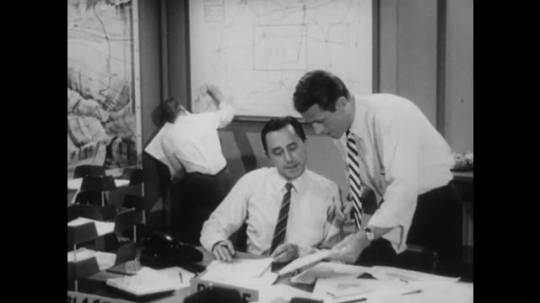 United States: 1950s: Men work at desk in office. Man draws on whiteboard. Men compare notes. Newsreader reads paper to microphone.