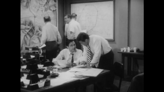 United States: 1950s: Men work in emergency response office. Man brings update information to colleague. Men update information on white board.