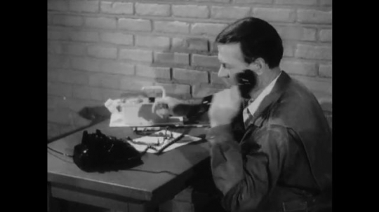 United States: 1950s: side profile as man picks up telephone on desk. Man dials phone number. Man puts on glasses.
