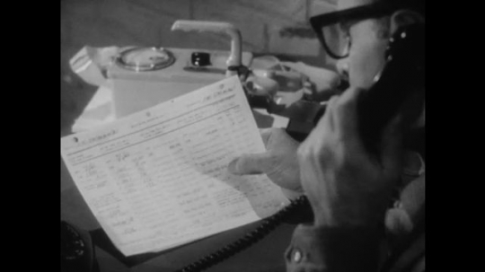United States: 1950s: Close up of paper as man makes phone call. Man speaks on telephone. Diagram shows nuclear fallout stations