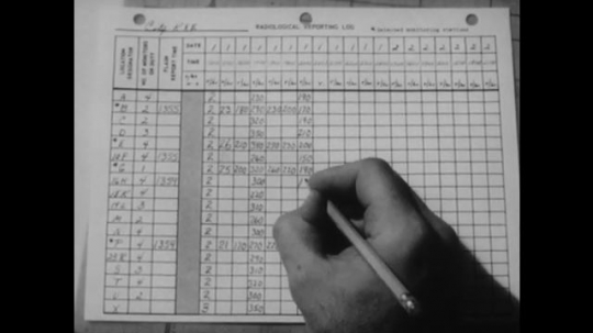 United States: 1950s: Hand writes pencil notes on logbook. Nuclear fallout chart. Close up of fingers writing numbers with pencil.