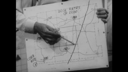 United States: 1950s: Man points at map of radiation dose rates. Drawing of nuclear shelters on map. Chart shows dose rate at radiation monitoring stations.