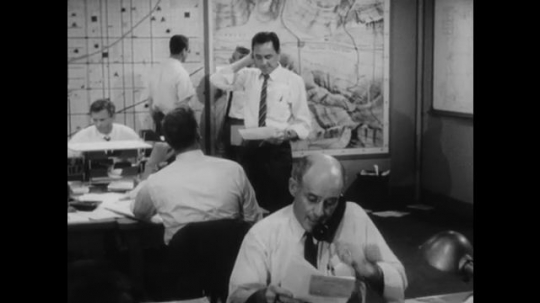 United States: 1950s: Men work in post nuclear attack emergency information office. Man broadcasts to public.