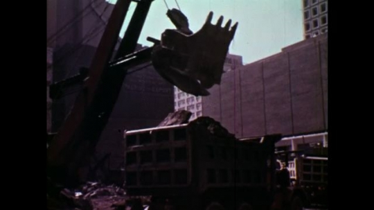 UNITED STATES: 1970S: digger clears rubble from building site. Crater n city. Building of a skyscraper in city.
