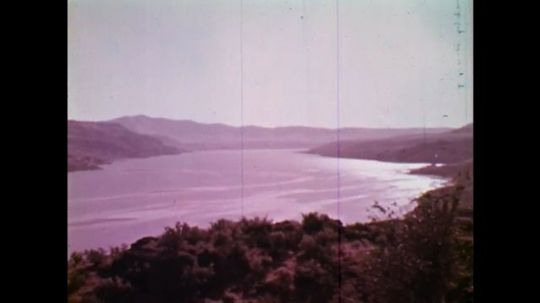 UNITED STATES: 1970S: view across lake and mountains in Columbia. Photo of construction work on dam.