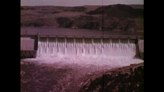UNITED STATES: 1970S: dam across gorge in Columbia. Water falls down dam wall.