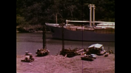 UNITED STATES: 1970S: ship on waterway. Men work on boat.